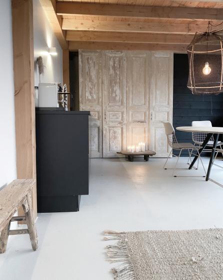 De houten deuren en het zwarte keukenblok zorgen voor een mooi contrast in het eetgedeelte
